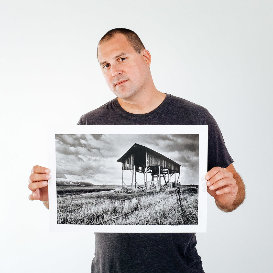 "Matt Mikulla holding the black and white print ""Skeleton"""