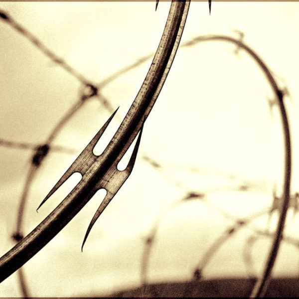 Containment - A Gritty and Industrial Photo of Razor Wire Fencing